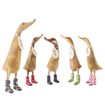 håndskårede træ-ænder med gummistøvler på